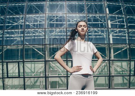 Confident Slender Girl In A White T-shirt Is Practicing Outdoors, Getting Ready For A Marathon