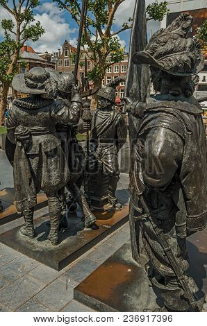 Bronze Sculpture Of Xvii Century Soldiers On The Rembrandt Square In A Sunny Day At Amsterdam. The C
