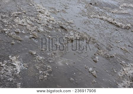 Damaged Asphalt Road With Potholes Caused By Freezing And Thawing Cycles During The Winter. Poor Roa