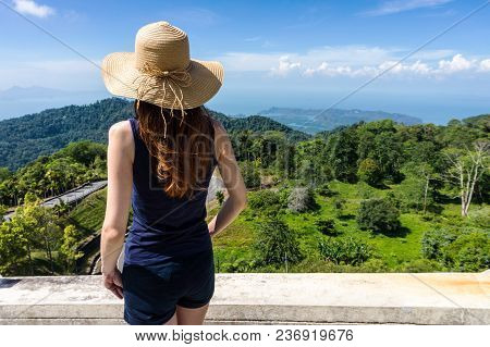 Young Traveling Woman In Hat And Standing On Edge Of The Mountain Cliff Before Beautiful View Of Hil