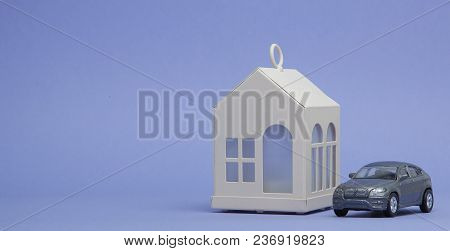 Gray Machine Model And Home On A Purple Background. Concept Of Lending, Savings, Sale, Lease Of Prop