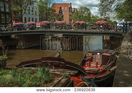 Amsterdam, Northern Netherlands - June 26, 2017. Bridge Over Canal With Moored Boats, People And Cyc