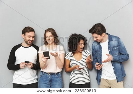 Photo of emotional group of friends standing isolated over grey wall background using mobile phones chatting.