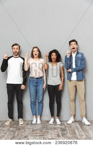 Photo of shocked group of friends standing isolated over grey wall background looking camera have an idea.
