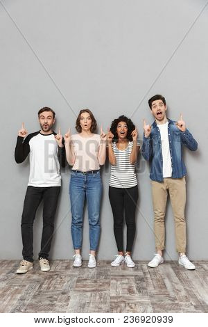 Photo of shocked excited group of friends standing isolated over grey wall background looking camera pointing.
