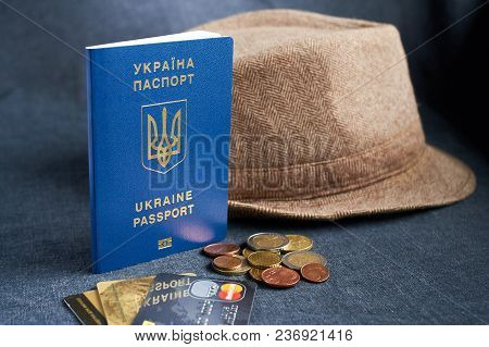 Ukraine Passport With Euro Bills Inside. On A Gray Background With Half And One Filler Eu Coins.