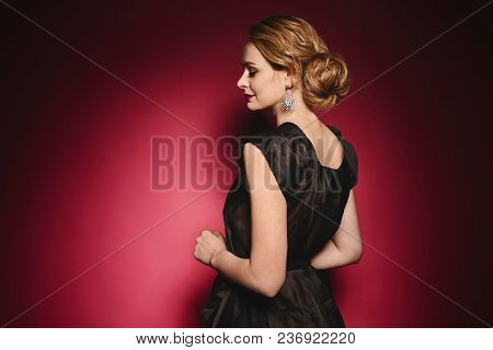 Beautiful Young Lady In Elegant Black Dress With Evening Makeup And Earrings Posing Back With Closed