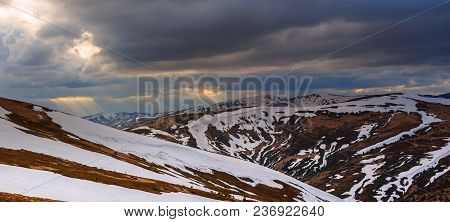 Spring Mountain Landscape With Snow, Panoramic View. Dramatic Clouds Lying On The Horizon And Sun Is