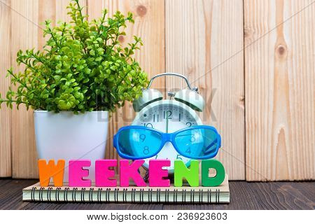 Weekend Letters Text And Notebook Paper, Alarm Clock And Little Decoration Tree In White Vase On Woo