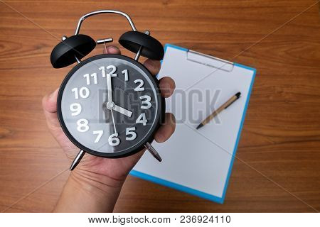 Black Vintage Alarm Clock In Hand With Clipboard And Blank White Paper And Pen, Copy Space For Add Y