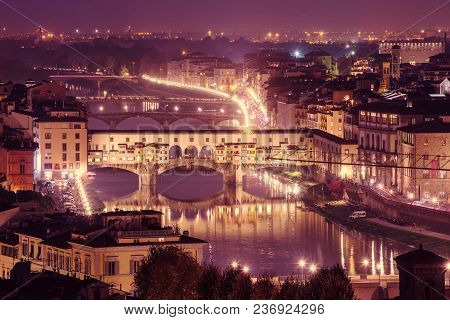 Night view of Florence city with Ponte Vecchio over river Arno and illumination. Travel sightseeing background. poster