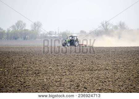 The Tractor Harrows The Soil On The Field And Creates A Cloud Of Dust Behind It.