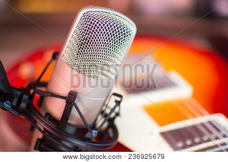 Microphone In Home Recording Studio With Red Guitar On Background