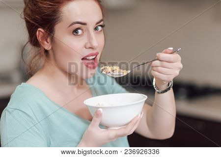 Beautiful Pregnant Woman Eating With Lust Cereals On Breakfast, Enjoying Meal. Yummy Food For Pregna