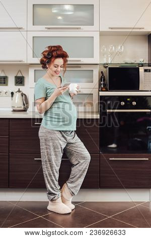 Smiling, Pregnant Woman Using A Smartphone, Looking To Screen, While Holding A Cup Of Tea Or Coffee