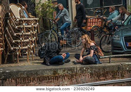 Amsterdam, Northern Netherlands - June 26, 2017. Street And Young People Talking Sitting By The Cana