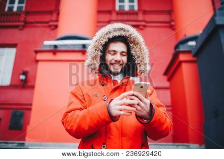 Handsome Young Male Student With Toothy Smile And Beard Stands On Red Wall Background, Facade Of Edu