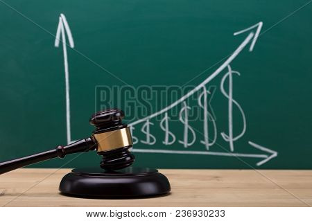 Close-up Of A Gavel In In Front Of Blackboard Showing Increasing Dollar Graph
