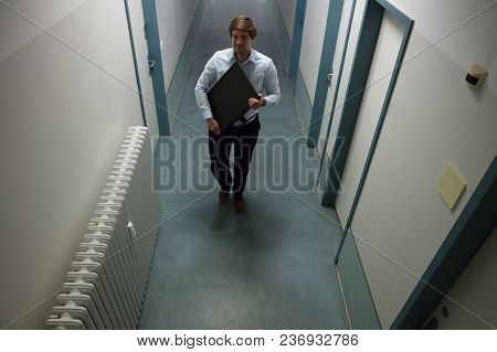 Young Man Stealing Computer Monitor Walking In Building Corridor