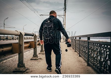 Male Photographer Traveler With Backpack And Camera In Hand Walking On City Bridge, View From Back,