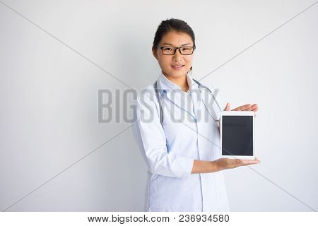 Smiling Young Asian Female Doctor Showing Tablet Computer Screen. Healthcare And Technology Concept.