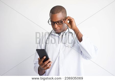 Serious Black Male Doctor Reading News On Smartphone. Technologies In Medicine Concept. Isolated Fro