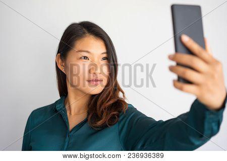 Beautiful Asian Girl Taking Self Portrait For Social Media Profile. Pensive Young Woman Having Video