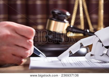 Close-up Of Robotic Hand Assisting Person In Filling Form Over Desk