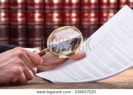 Human Hand Examining Document Through Magnifying Glass