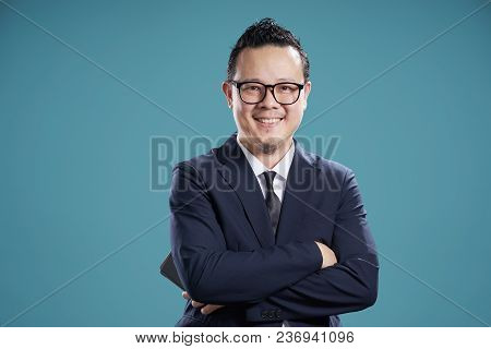 Portrait Of Smile Asian Businessman In Suit . Isolated On Light Blue Background .