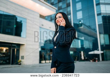 Businesswoman in suit talks by mobile phone outdoor, business center on background. Modern financial building, cityscape. Successful female businessperson