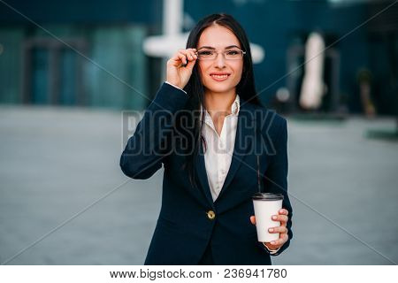 Portrait of young, beautiful business woman in glasses and suit with laptop in hands. Modern building, financial center, cityscape. Successful female businessperson