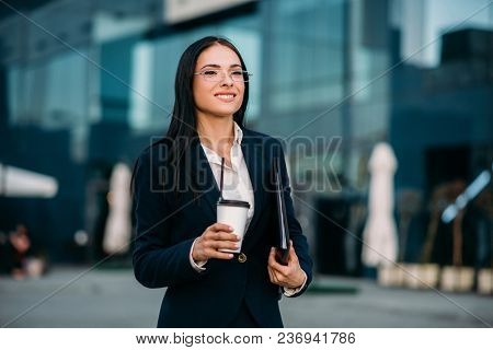 Business woman in glasses with coffee in hands, against skyscraper. Modern building, financial center, cityscape. Successful female businessperson