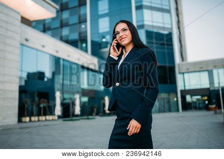Businesswoman in suit talks by mobile phone outdoor, business center on background. Modern financial building. Successful female businessperson
