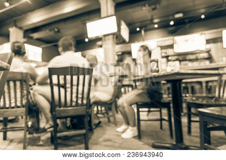 Blurred people gathering and watching American football in a sport bar/pub at Bourbon Street in New