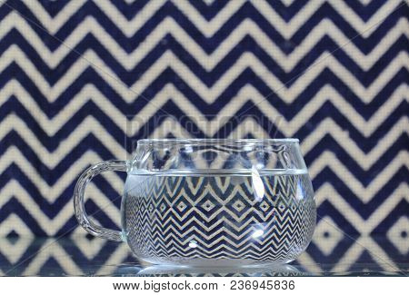 A Cup With Water On A Zig Zag Pattern Background.