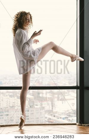 Young Slender Ballerina In Her Underwear And Pointe Shoes By Window. She Stands On Tiptoe. Girl Is H