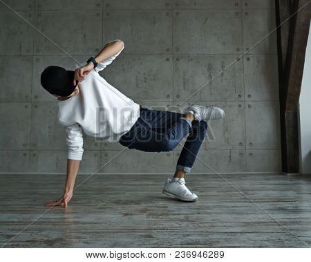 Teenage Boy In White Sweater And Baseball Cap, Jeans And Sneakers Makes Breakdance In Dance Studio.