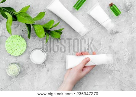 Natural Cosmetics For Skin Care Near Green Leaves On Grey Background Top View.