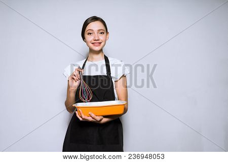 Beautiful Young Woman Cook In A Black Apron Prepares A Delicious Cake And Smiles