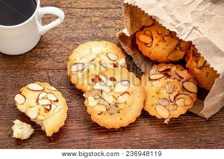 a bag of French almond cookies and espresso coffee against weathered  wood background