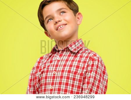Handsome toddler child with green eyes confident and happy with a big natural smile laughing looking up over yellow background