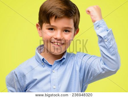 Handsome toddler child with green eyes happy and excited expressing winning gesture. Successful and celebrating victory, triumphant over yellow background
