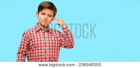 Handsome toddler child with green eyes unhappy making suicide gesture, tired of everything. Shoots with hand imitating gun, upset over blue background