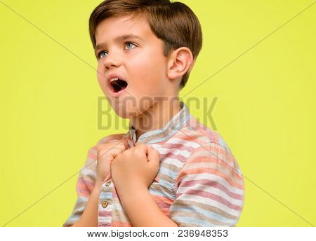 Handsome toddler child with green eyes happy and excited celebrating victory expressing big success, power, energy and positive emotions. Celebrates new job joyful over yellow background