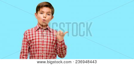 Handsome toddler child with green eyes happy and surprised cheering expressing wow gesture pointing up over blue background