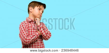 Handsome toddler child with green eyes thinking and looking up expressing doubt and wonder over blue background
