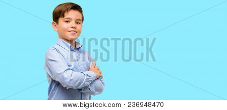 Handsome toddler child with green eyes with crossed arms confident and happy with a big natural smile laughing over blue background