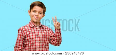 Handsome toddler child with green eyes raising fingers, number two over blue background