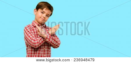 Handsome toddler child with green eyes annoyed with bad attitude making stop sign crossing hands, saying no, expressing security, defense or restriction over blue background